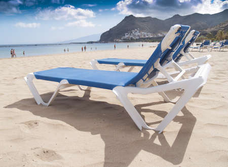vacation concept: beach chairs on white sand on the shore of ocean Stock Photo