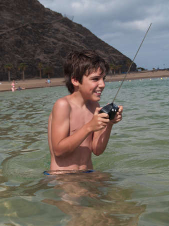 happy boy playing with remote control toy in ocean