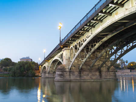 Triana Bridge, the oldest bridge of Seville, Spain at dusk Stock Photo