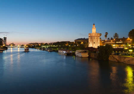 Blick auf den Fluss Guadalquivir in Sevilla, Spanien mit Golden Tower (Torre del Oro) und Triana Br�cke bei Nacht
