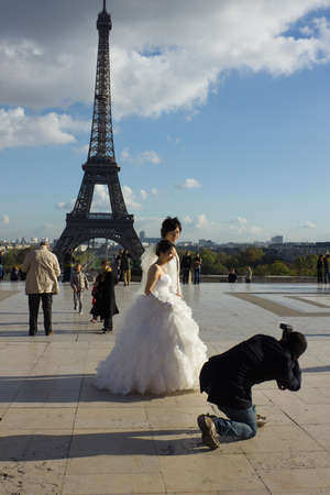 a meeting with a view to marriage: PARIS, FRANCE - NOVEMBER 06: shooting wedding of young couple in Paris on November 6, 2012 in Paris, France. Classic view of Eiffel tower is popular for marriages from all over the world.