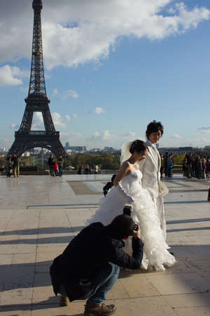 PARIS, FRANCE - NOVEMBER 06: shooting wedding of young couple in Paris on November 6, 2012 in Paris, France. Classic view of Eiffel tower is popular for marriages from all over the world.
