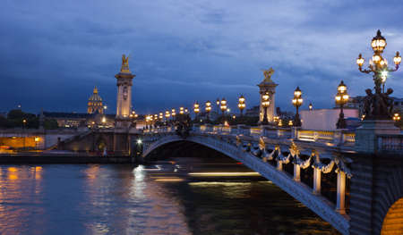 Alexander the Third bridge and Seine with golden Invalides dome and lights of cruise boat at night in Paris
