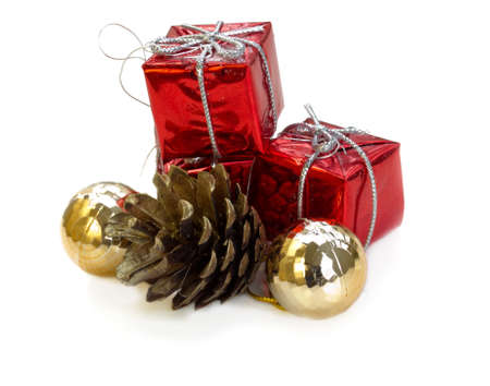 red christmas gifts with golden balls and firtree cone isolated on white