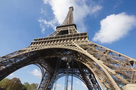 sunlit Eiffel Tower, Paris, against blue sky from below Stock Photo