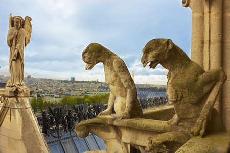 Famous figures of gargoyles and angel of Notre Dame (built in 1240) over Paris aerial photo