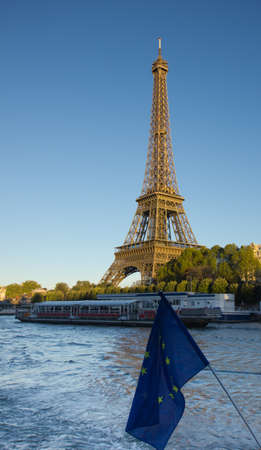 Eiffel Tower, Paris, at sunset as seen from Seine river with EU banner
