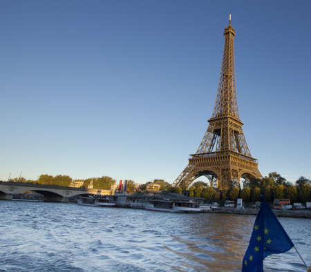 Eiffel Tower, Paris, at sunset as seen from Seine river with EU banner photo