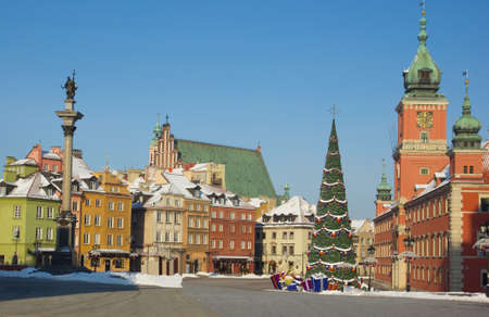 Castle square of Warsaw, Poland with palace, king Sigismund column and colorful medieval houses in winter, decorated for christmas
