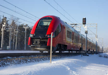 High-speed modern commuter train riding among snowed forest Editorial