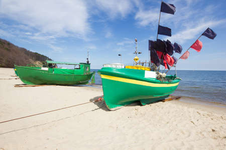 polska: colorful fisher boats on Baltic beach under blue skies