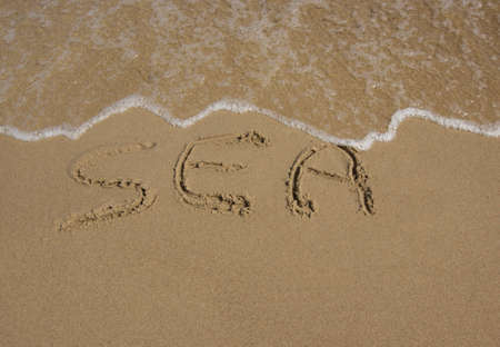 sea written on sand vacation concept