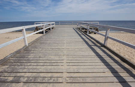a wooden pier over the sea on lonely beach of Baltic photo