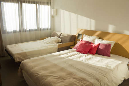 simple budget bedroom with two beds with red pillows and window