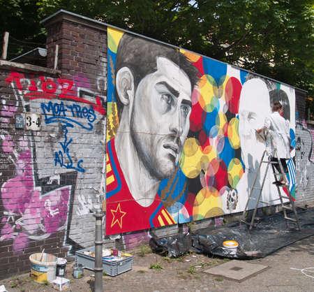 BERLIN - 29. Mai: Junger Maler machen Zeichnung auf West Side Berliner Mauer am 29. Mai 2013 in Berlin. Editorial