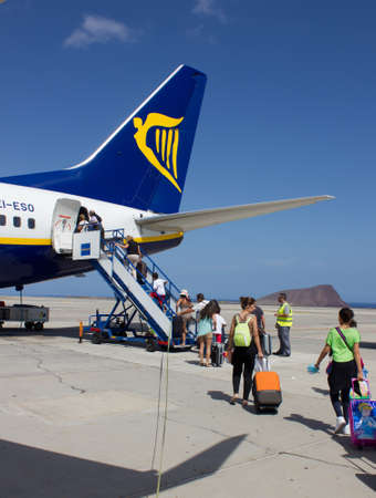 TENERIFE - JULY 16, 2014: Passеngers boarding Ryanair flight, on July 16, 2014 in Tenerife. Ryanair is biggest budget low-cost airline in the world.