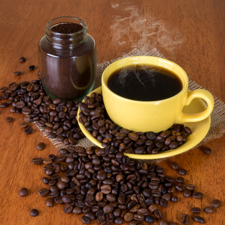 coffea: Cup of coffee with saucer, pot with coffee and coffee beans on the table