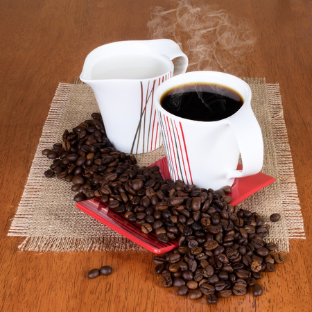 coffea: Cup of coffee with saucer, milk jug and coffee beans on the table