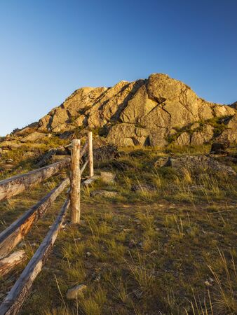 non urban: Wooden fence and stone hill in the light of the setting sun