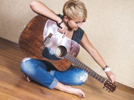 tunes: Young girl in jeans and a denim vest sits on a floor and tunes the guitar