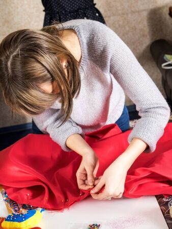 needlewoman: Young girl sews the dress in the atelier