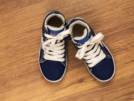 footgear: Pair of blue childrens sneakers on the wooden floor Stock Photo
