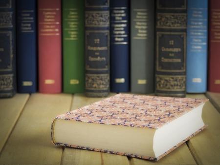 Chiuso il libro di fronte a diversi libri sul tavolo