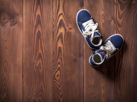 Par de zapatillas de deporte de los niños azules en el suelo de madera Foto de archivo
