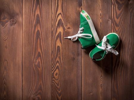 Par de zapatillas de deporte de los niños verdes en el piso de madera