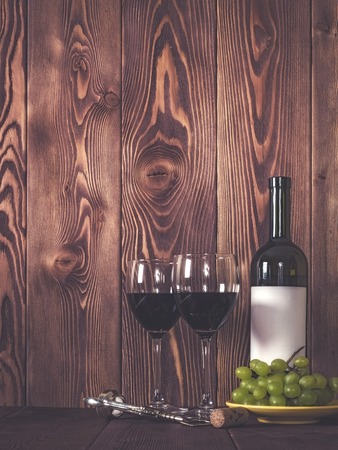 wine gift: Bottle of wine, wineglasses and grape on wooden table. Retro style. Dark toned Stock Photo