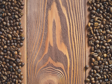 coffea: Multiply coffee beans on the wooden table. Top view