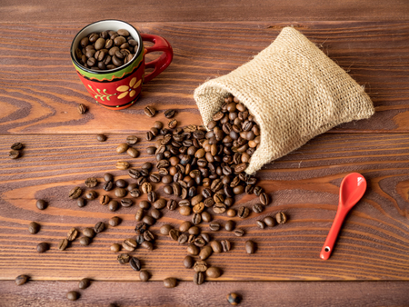 coffea: Cup with saucer and bag with coffee beans on the wooden table Stock Photo