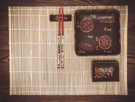 japanese cookery: Bamboo mat, plates and chopstick on the wooden table. View from above