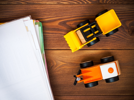 unnecessary: Toy tractor on the wooden floor near the pile of unnecessary paper. View from above