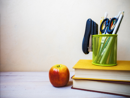 View on the pile of books, apple and cup with pencils lying on the wooden table Stock Photo