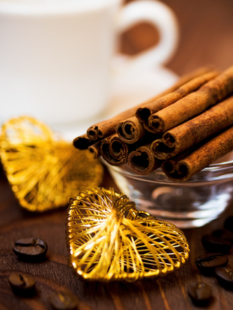valentine day cup of coffee: Cup of coffee, cinnamon sticks and coffee beans on the table. Saint Valentines day concept