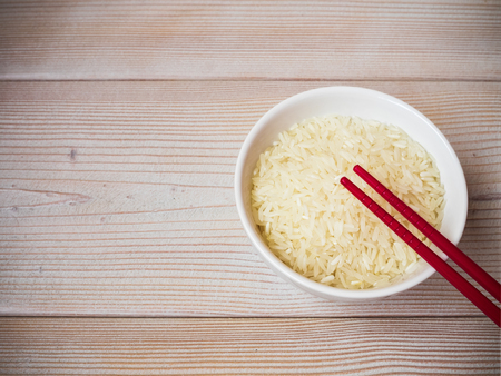 japanese cookery: Ceramic bowl with uncooked rice and red chopsticks on the wooden table