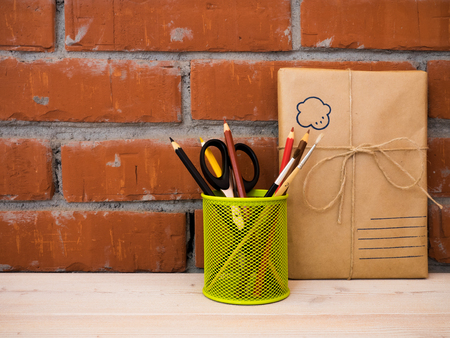 over packed: Still life with packed gift and colored pencils on wooden table over brick background Stock Photo