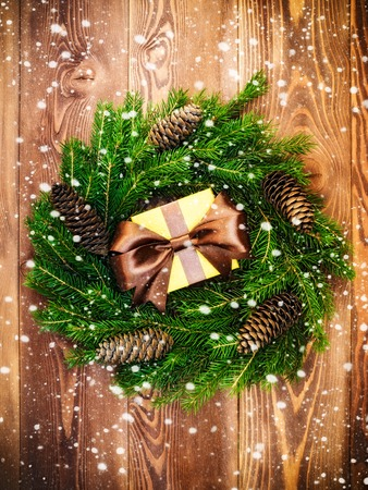 Christmas wreath of fir branches with cones along with gift box on the wooden background. Drawn snow. Top view. Holiday concept Stock Photo