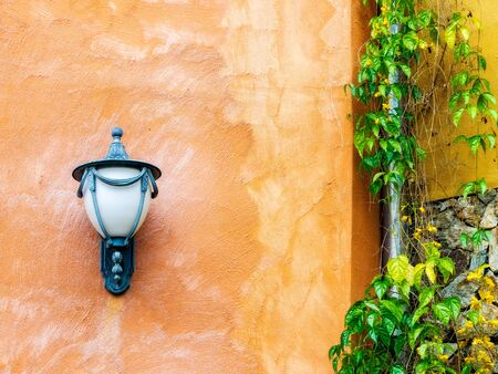 Stone wall with the lantern, downpipe and ivy on it Stock Photo