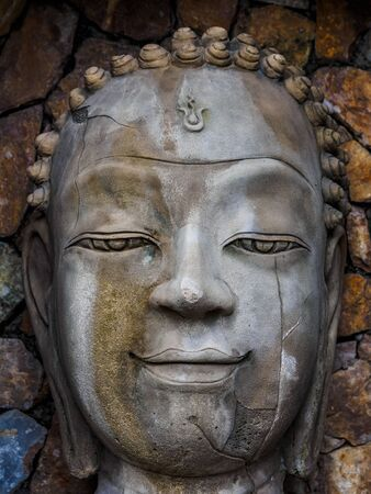 Sandstone face of Buddha in the niche of the wall