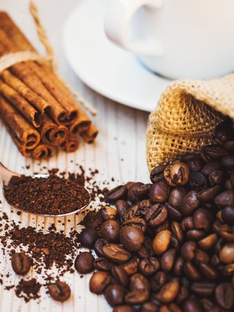 Cup of coffee, pouch with coffee beans, cinnamon sticks and spoonful of ground coffee on the wooden table. Shallow focus