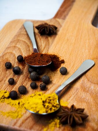 Spoons with turmeric and paprika powder, black pepper and star anise on the cutting board. Shallow focus