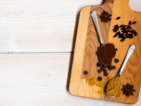Spoons with turmeric and paprika powder, black pepper and star anise on the cutting board. Shallow focus. Top view Stock Photo