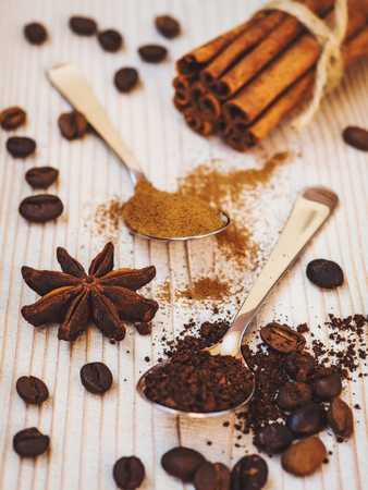 Spoonfuls of ground coffee and cinnamon, cinnamon sticks, coffee beans and star anise on the wooden background
