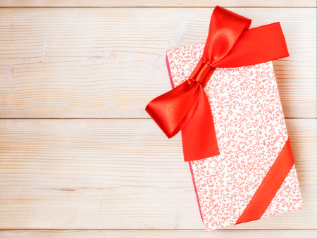 Birthday present with red satin tape on wooden board. Holidays concept