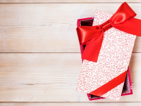 Christmas present with red satin tape on wooden board. Holidays concept