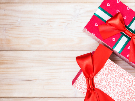 Wrapped in cloth gift boxes with bow on wooden board. Holidays concept