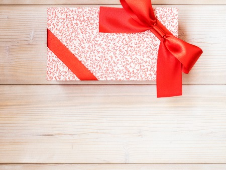 New year present with red satin tape on wooden board. Holidays concept