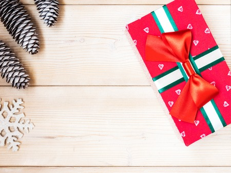 Christmas theme with fir cones along with gift box on the wooden background. Top view. Holiday concept Stock Photo